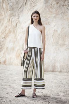 Top Philo. One shoulder raw silk top with asymmetric darts. Trousers Dokos. Wide leg culotte style trousers with bottom contrasting panel and back slit. Sandals Hephaestus. Signature calf leather block cutout sandals. #zeusndione