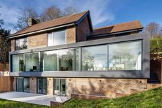 AR Design Studio has extended a 1970s house in Hampshire, England, with two glass-fronted volumes featuring huge windows.