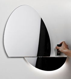 OPEN MIRROR BY DIGITAL HABIT(S). In the closed position the mirror is oval-shaped. Slide the mirror open to reveal a docking station for your iPhone or iPod to connect. The best thing about it is that it's controlled by hand movements, which means you can even have wet hands. Your various hand movements can control the volume, skip to the next song, or even pause the song you're on.