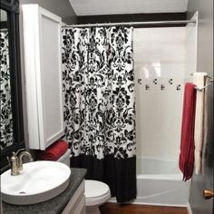 Batik Motif Black And White Shower Curtain for Modern Bathrooms & Bath Towels on the Towel Rack & Clean Hygienic Toilet with Towel and Medicine Cabinet & Wooden Vanity with Drop In Sink on the Marble Countertop and Single-hole Faucet