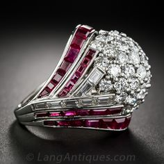 Art Deco/Retro Style Diamond and Ruby Cocktail Ring. A large platinum dome, aglitter with fine white brilliant-cut diamonds blooms from elegant flares of channel-set calibre-cut rubies and baguette diamonds.This spectacular showstopping cocktail ring gives off sparks form all angles and with every movement. The ring measures about 7/8 inch in length and in width. Total diamond weight is 4.50 carats...