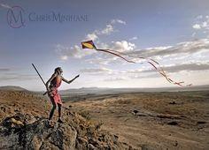 A Maasai warrior flies a kite over the Rift Valley, Kenya. Africa. Chris.minihane@gmail.com