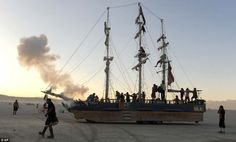 A sailboat art car fires off a round at the Burning Man festival where tens of thousands of participants have gathered for the counterculture event