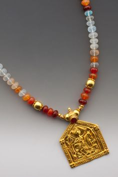"Intentionantique 20K-22K Indian plaque amulet of Bhumiya Raj with a bezel-set orange glass stone that playfully interacts with the variegated shades of very ""gemmy"" faceted semi-transparent Mexican fire opal."