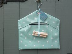 Oilcloth peg bag in aqua spot design, complete with dolly pegs. From www.etsy.com/dagenaisdesign