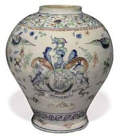 AN ENGLISH DELFT ARMORIAL POLYCHROME APOTHECARY JAR CIRCA 1695-1715, PROBABLY LONDON Of baluster form, painted in blue, pale-green, red and yellow with the arms of the Worshipful Society of Apothecaries above the motto OPIFERQUE PER:ORBEM DICOR on a scrolling banner, among birds, insects and mythical beasts, the reverse with a two-handled vase issuing flowers between bands of scrolls and scattered sprigs