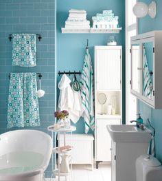 Turkoosisävyinen kylpyhuone, jossa pyyhkeitä hyllyillä, tangoilla ja koukuissa.