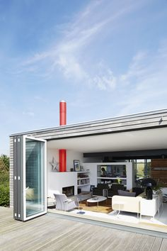 A home near Rye, England, opens onto a deck through a Sunflex door. The living room features a sofa by  Terence Woodgate, 620 chairs by Dieter Rams for Vitsœ, and an Oluce Atollo 239 lamp by Vico Magistretti.