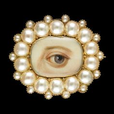"""Oval brooch and pendant surrounded by 14 split pearls with 14 small satellite pearls; brown left eye. Inscribed initials on reverse: """"J.A.T.,"""" """"W.V.T.,"""" """"J.M.T."""" Circa 1835–40."""
