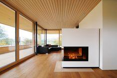 Ein währschafter, nach drei Seiten verglaster Holzofen trennt den  Essplatz vom Wohnraum.