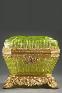 Un beau coffret en cristal de couleur ouraline avec sa clef et monture en bronze doré. De forme trapézoïdale à pans coupés, il présente un décor taillé à fines nervures, aux motifs ondulants et à motif rayonnant au sommet du couvercle.  c.1880   Le terme « ouraline » désigne un objet en verre ou en cristal de couleur jaune avec des reflets verts.