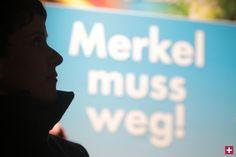"""AfD-Chefin Frauke Petry vor einem Plakat mit der Aufschrift """"Merkel muss weg"""""""
