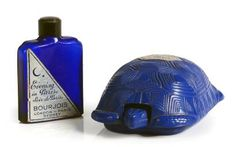 «Evening in Paris» - (Australie) Rare coffret en résine moulée thermoformée de couleur bleu nuit représentant une tortue de terre avec son étiquette argent, contenant son flacon d'extrait en verre teinté bleu nuit avec capsule en résine noire et étiquette argent. h: 5 cm (flacon)