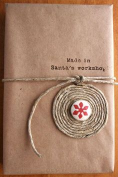 """Wrap twine in circles around a Christmas-themed button for a rustic finish. Plus, add a """"Made in Santa's Workshop"""" stamp to take it to the next level. Get the tutorial at Cosmo Cricket."""
