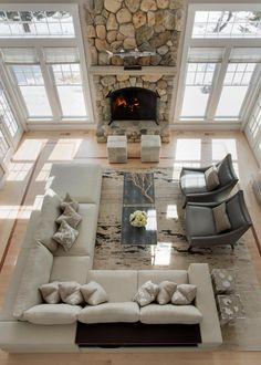 A dramatic floor to ceiling stone fireplace is the focal point in this two-story coastal style living room. A neutral sectional and wood coffee table add a touch of contrast to the bright look of the space, including soft beige walls and large windows that allow natural light to flood the room.