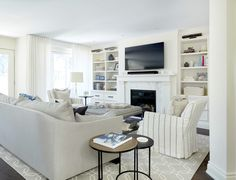 White and gray living room features a gray curved arm sofa facing a gray linen tufted ottoman as coffee table flanked by white and gray striped arm chairs adorned with ruffled pillows. Living Room White, White Rooms, Living Room Colors, Living Room Sofa, Living Room Designs, Living Area, Living Spaces, Striped Room, Striped Chair