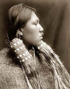 You are looking at an intriguing picture of a Hesquiat Maiden. It was taken in 1910 by Edward S. Curtis.    The picture presents Hesquiat woman, head-and-shoulders portrait, right profile.