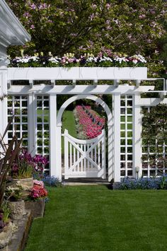 Garden gate and arbor in spring with tulip border, forget me nots, stone urns, planters and apple tree