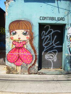 fuckyeahlatinamericanhistory:    atrapaluz:    Gran Avenida casi llegando a Americo Vespucio. Una hermosa niña de grandes ojos. contrasta con la derruida oficina de contabilidad. esta cerca de un trabajo de Aislap, se leas ha visto trabajando juntos en otras partes. La firma está abajo pero no se entiende mucho ¿Alguien sabe quién es?    Street art in Santiago de Chile.