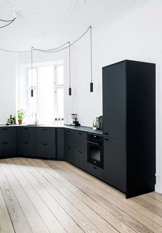 Modern kitchen with cabinetry and drawer fronts in black linoleum and integrated pulls/cut outs for handles. We love the bright hardwood floors. Home & Kitchen - Kitchen & Dining - kitchen decor - http://amzn.to/2leulul
