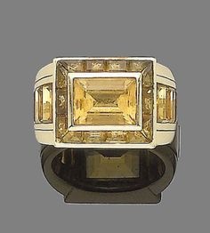 A citrine ring, by Hemmerle  The rectangular plaque, collet-set with a step-cut citrine, within a surround and shoulders of similarly-cut stones, to a wide tapering band