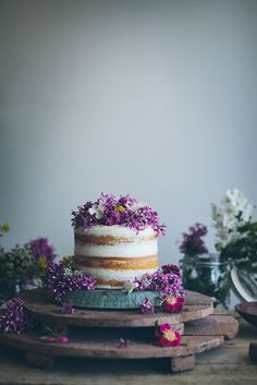 A minimal cake top with purple edible flowers sweetens up a rustic wedding.