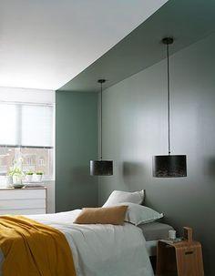 Vous installez votre lit dans un renfoncement  ? N'hésitez pas à souligner cette installation en peignant le mur dans une couleur contrastée  et en installant deux suspensions design... comme dans un hôtel de charme !