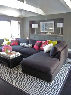 Love the idea of a neutral piece of furniture with bold accessories. Makes it so easy to change up the look of the room for cheap! This looks great with the patterned pillows and rug.
