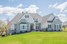 Custom home with real stone veneer, board and batten shutters, and a stained front door.