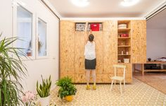 Sliding chipboard units create multifunctional space in Madrid apartment