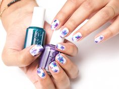 Get floral with this beautiful watercolor nail art with the new silk watercolor collection from essie. Recreate this look with two coats of 'white page' as a base and let dry. Using 'no shrinking violet' purple use light strokes to create the petals of a flower, and a similar effect on top with 'pen & inky' teal. Add a dot of red 'highest bidder' in the center of the flower. Top it off with essie gel•setter.