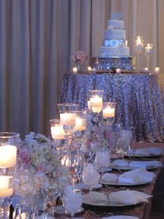 A silver and white wedding cake sits upon a sequin-covered cake table. Flowers, decor and rentals by Posh Peony Floral and Event Design.