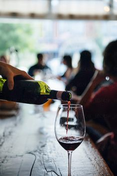 Bartender pours a glass of red wine at a bar by Cara Dolan for Stocksy United