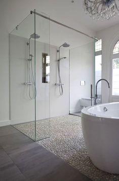 Clean white bathroom using white pebble tile floor in shower and as flooring.