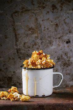 Caramelized sweet popcorn served in vintage enameled white mug with pouring caramel over old dark iron rusty background.