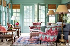 In the sunroom, a pair of barrel-back armchairs clad in a Brigitte Singh fabric flank a custom-made ottoman. The Chinese cloisonné floor lamps are topped with custom-designed shades; the room is painted in Farrow & Ball's Folly Green.