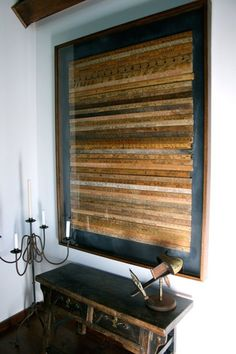A collection of vintage yard sticks are framed and hung as art on a wall.
