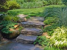 The boulder stepper staircase, flanked with natural boulders on both sides, and a bluestone flagging pathway to the deck have open views to the lawn and lush foundation plantings.