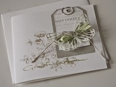 hand crafted card by Mia ... collage montage in soft grays and green ... die cut butterfly and tags wit stamping and more ...