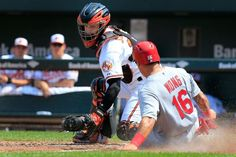 BALTIMORE, MD - AUGUST 10: Kolten Wong #16 of the St. Louis Cardinals slides safely into home plate as catcher Caleb Joseph #36 of the Balti...