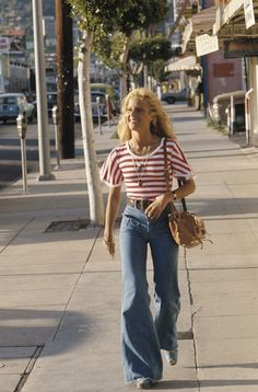 In Los Angeles, 1976 mid 70s vintage fashion day casual sports wear jeans wide leg bell bottoms sneakers red white strip top shirt found photo print girl on street