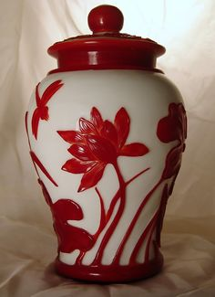 Chinese antique Peking glass red and white lidded ovoid jar with a high relief lotus flower and dragonfly design. Made in the era of Emperor Tao Kuang of the Ching Dynasty of China, about 1820.
