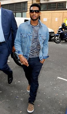 Usher in Dita Insider sunglasses, YSL Mojave Leopard printed cowhide lace-up chukka sneakers  Levis denim trucker jacket, a Comme Des Garcons striped metallic long sleeve t-shirt  and navy cargo pants.