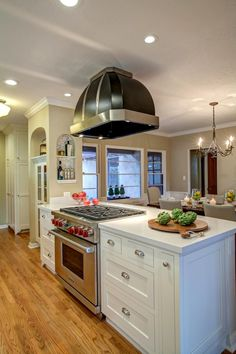 A stainless steel oven pairs with a retro black range hood in this vintage modern kitchen. White cabinets are topped with white countertops for a timeless look, while a lovely dining area behind the island allows the chef to prep, cook and entertain all in one spot.