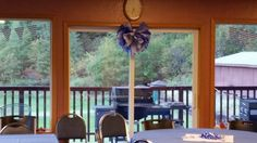 """We needed a few simple decorations but with so many coming from out of town, we did 1 big tissue """"puff ball"""" and supplemented with two more Dollar Tree """"puff balls""""  we hung on the windows.  A couple of pennant strings for the windows and we called it good!  Colored tablecloths will really make a room come alive!"""