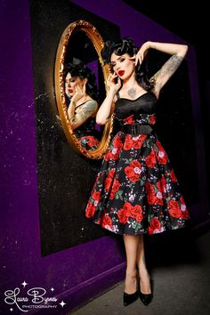 Courtesan Swing Dress in Red Rose Print - The Courtesan Dress was inspired by 1950s lingerie with its vintage corset and girdle styling. The bust features a mesh overlay, velvet trim, and a black velvet bow detail. The straps are adjustable for the best possible fit, and the cups of the bust are slightly padded to create the sexy silhouette of a great 1950s bra. The bust is lined in stretch charmeuse and it is finished off with a back zip and a removable wide belt. Stunning in our exclusive…