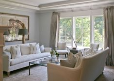 Gorgeous transitional seating area with two white sofas, a glass and metal coffee table and a pair of accent chairs. Soothing greys, whites and greens keep it relaxing.