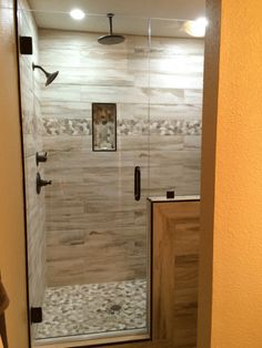 Master Shower with Wood plank tile, flat river rock deco band and floor, recessed niche and oil bronze plumbing fixtures.