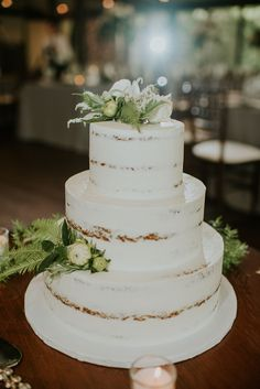simple naked wedding caked embellished with greenery | Image by Mallory + Justin