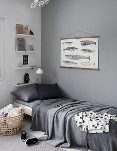 sleek design. sleeping. the gray walls. gray plaid. comfort. the Scandinavian style. Nordic design. whales. picture. shelves. lighting